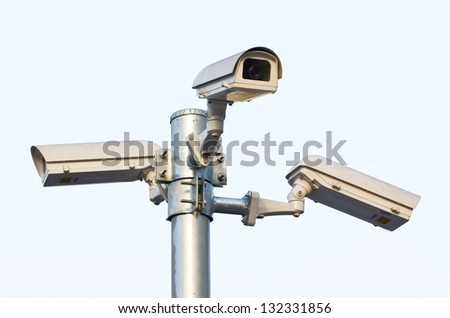 Three security cameras against the sky. - stock photo