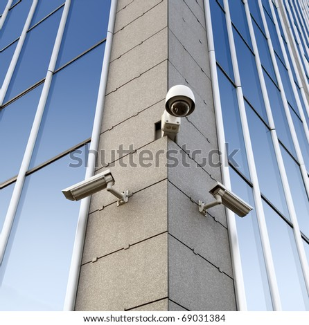 Three security cameras attached on the office building corner - stock photo