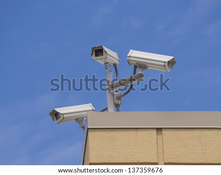 Three security cameras on a building against blue sky - stock photo