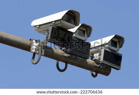 Three security surveillance cameras isolated on blue.