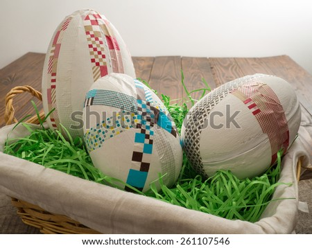 Three selfmade easter eggs with colored taped on a wooden table with easter grass - stock photo