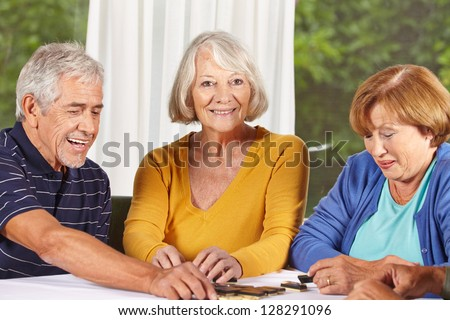 Three senior citizens playing a domino game in a nursing home - stock photo