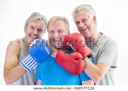 Three senior men posing in boxing gloves
