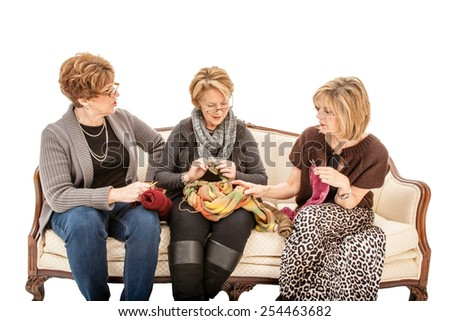 Three senior women sitting on a couch talking and knitting - stock photo