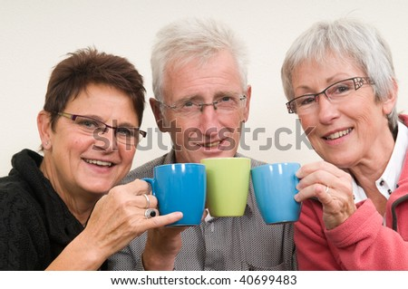 Three seniors holding a cup of coffee. - stock photo