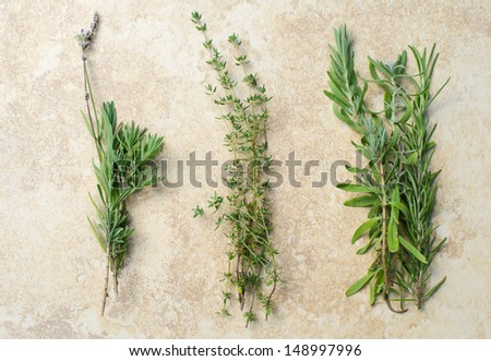 Three separate bunches of fresh garden picked organic lavender rosemary and thyme herbs on tan kitchen counter - stock photo
