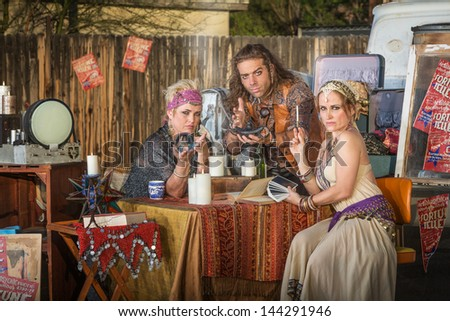 Three serious gypsy fortune tellers with outdoor kiosk - stock photo