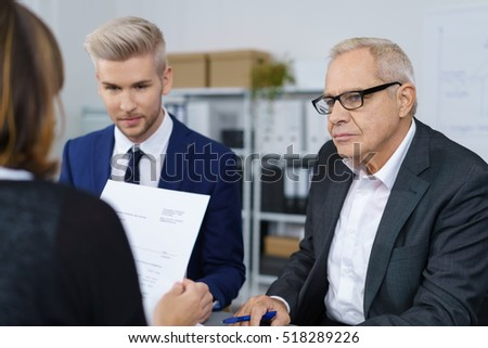 Three serious mature and young workers discussing business in small office with bookshelf in background