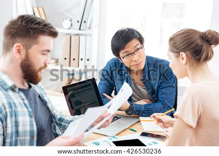 Three serious young businesspeople sitting and working in office together