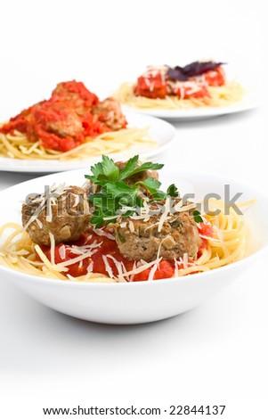 three servings of spaghetti with meatballs in tomato sauce on white plates - stock photo