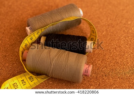 Three sew threads with a measuring tape on a cork table