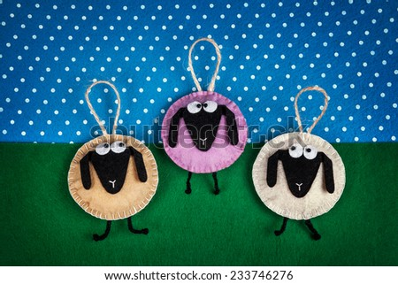 Three sheep toys from felt on green and blue background - stock photo