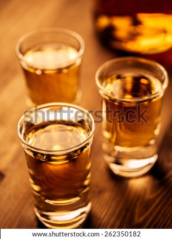 Three shots and a bottle on a table - stock photo