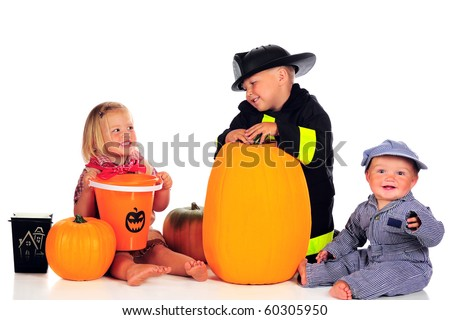 Three siblings dressed for Halloween as a cowgirl, fireman and train engineer with their pumpkins and trick-or-treat buckets.  Isolated on white. - stock photo