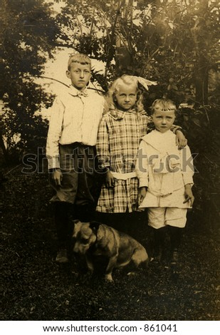 Three siblings in a vintage garden portrait with the family dog.  Original Circa 1909 print has scratches, artifacts, fading and solarization qualities. - stock photo
