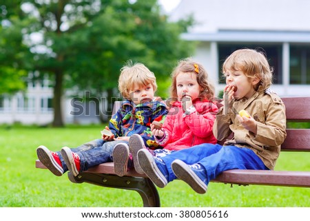 Three siblings sitting on bench and eating chocolate. Two littlke kid boys and girl having fun. Siblings and family - stock photo