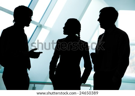 Three silhouettes of businesspeople interacting with each other in the office - stock photo