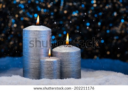 Three Silver Candles in snow with snowfall - stock photo