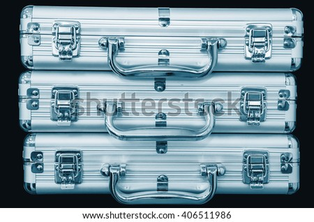 Three silver trunks on a black background. Blue colored - stock photo