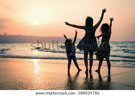 three sisters at the beach, sunset shot, rear view,