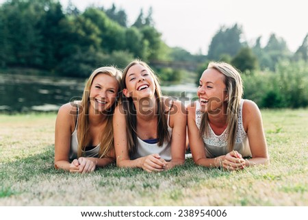 Three Sisters Laying Down in Grass Smiling and Laughing Hard - stock photo