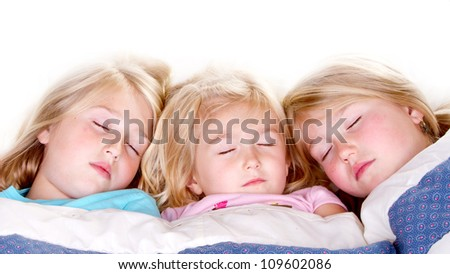 Three sisters sleeping or snuggling in bed - stock photo