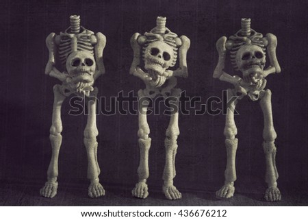 Three skeletons holding their own heads grungy textured - stock photo