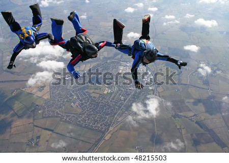 Three skydivers in a line behind each other with a town in the background - stock photo