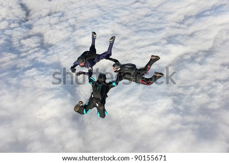 Three skydivers in freefall over bank of clouds - stock photo