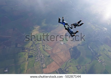 Three skydivers in freefall with sun lighting up the earth below through the clouds - stock photo