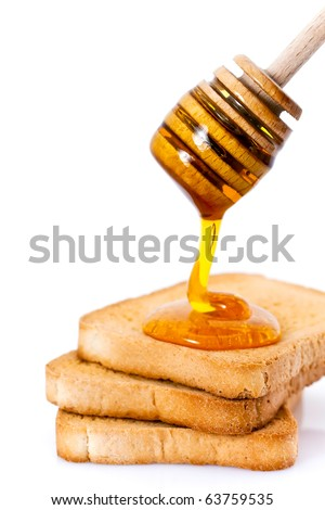 Three slices of toasted bread with honey and honey dipper isolated on white studio background.