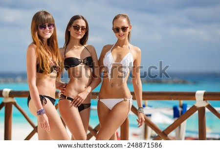 Three slim young girls in bikinis on the beach. Group of Three Beautiful Attractive Young Women Walking on the Beach. happy girl friends having fun at the beach while on vacation - stock photo