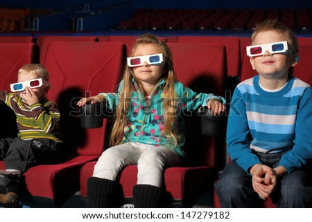 Three small children in 3D glasses watching a movie in the cinema - stock photo