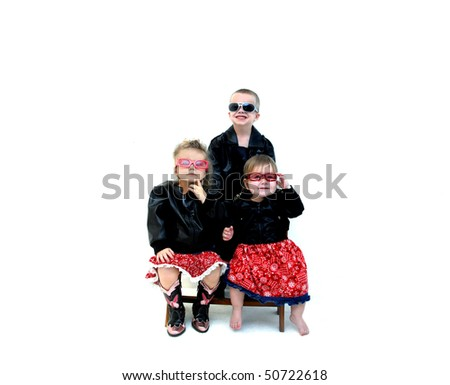 Three small children model leather coats and cool sunglasses.  Two sisters are sitting on a wooden bench with brother standing behind.  Two are smiling and one is not so sure.