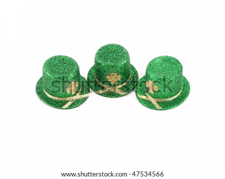 Three small green and gold top hats on white with copy room for Saint Patrick's Day - stock photo