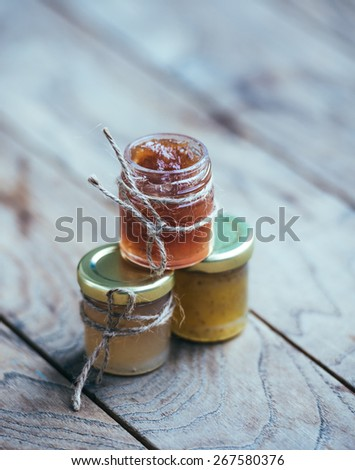 Three small jars of marmalade or jam on wooden table - stock photo