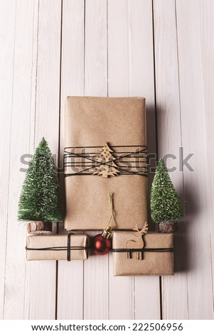 Three small presents with Xmas decoration. / Christmas handcraft gift boxes on wood background.  - stock photo