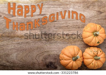 three small pumpkin with happy thanksgiving written on wood - stock photo