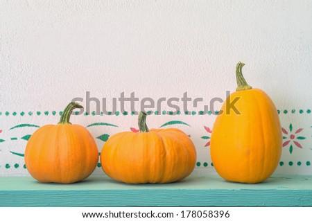 Three Small Pumpkins on Shelf - stock photo