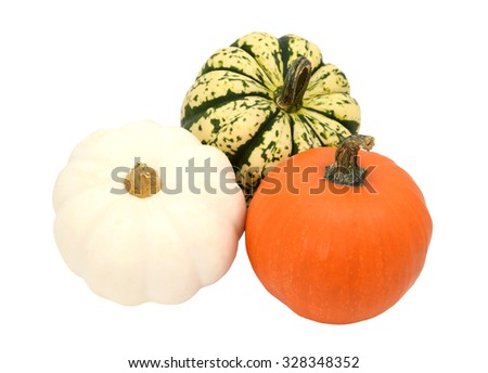 Three small pumpkins - orange, white and green striped gourds, isolated on a white background - stock photo