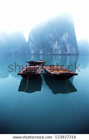 Three small row boats tendered behind a passenger Junk in a misty Halong Bay, Vietnam. - stock photo