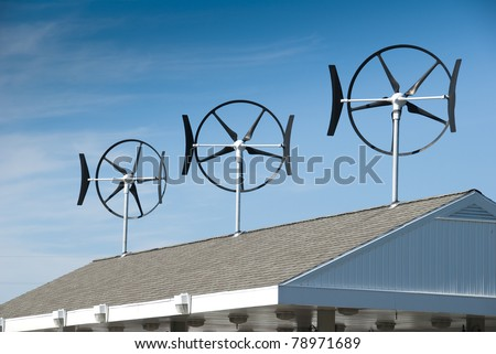 Three smaller wind turbines located on top of a gasoline station