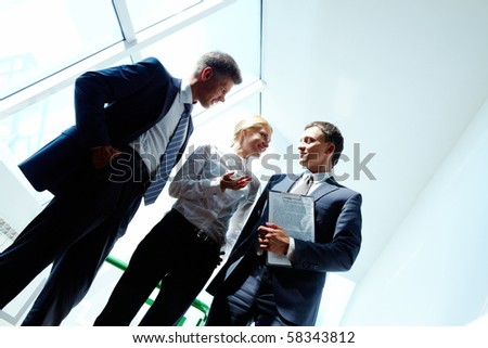 Three smart employees discussing new strategy at meeting - stock photo