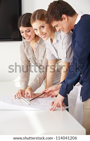 Three smiling architects working with a blueprint in their office - stock photo
