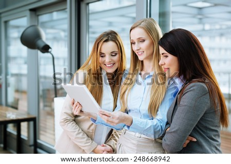 Three smiling business associates looking at a website on a tablet