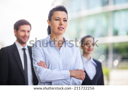 Three smiling business people standing outside. waist up of young business people looking - stock photo