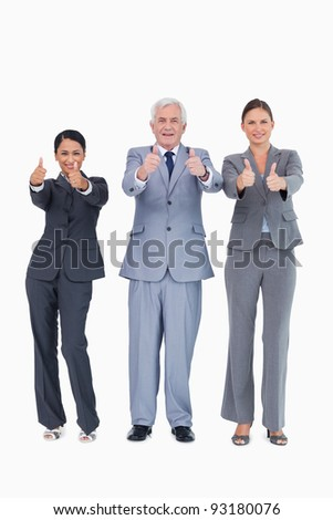 Three smiling businesspeople giving thumbs up against a white background - stock photo