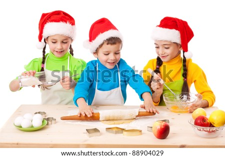 Three smiling children with Christmas cooking, isolated on white