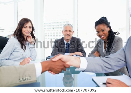 Three smiling colleagues looking at two executives shaking hands - stock photo