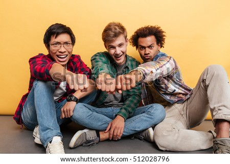 Three smiling confident young men friends sitting and joining their fists over yellow background